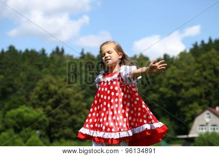 Little girl in a red polka-dot sundress into a major run on green field