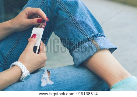 Girl In Jeans Sitting On The Bench And Connect The Headphones To Her Music Player