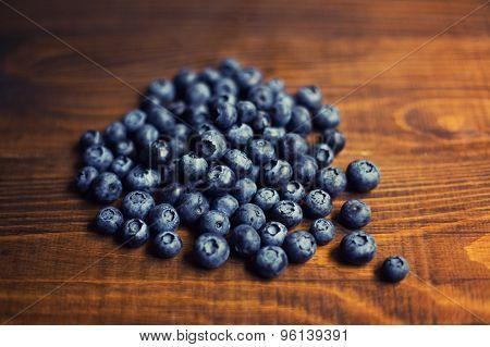 Fresh great bilberries on wooden ground