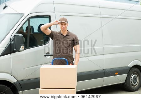 Delivery Man With Cardboard Boxes In Front Van