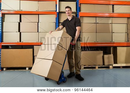Worker With Boxes On Hand Truck In Warehouse
