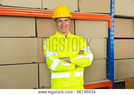 Happy Male Warehouse Worker With Arms Crossed