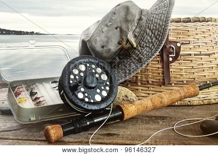 Hat and fly fishing gear on table near the water's edge