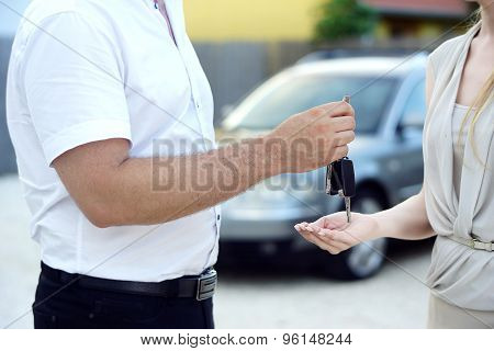 Car salesman give new car keys to customer