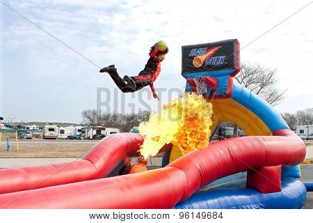 Man Jumps Over Fireball To Dunk Ball In Carnival Act