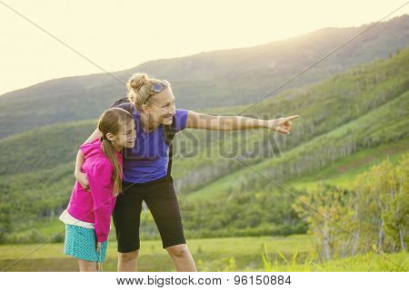 Family hiking in the mountains together. Young mother pointing out wildlife while she and her daughter take a hike together in the mountains on a beautiful summer evening
