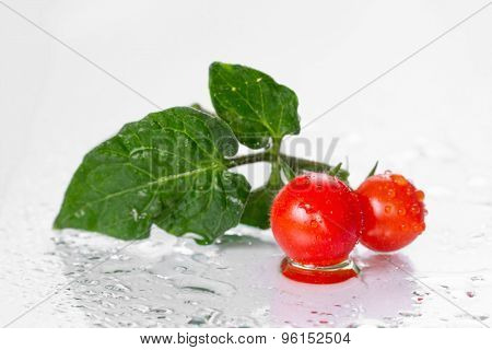 Two Cherry tomatoes with leaves and drops of dew.
