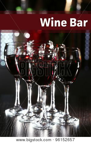 Glasses of red wine in bar on blurred background