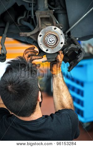 Mechanic Working On Car Brakes