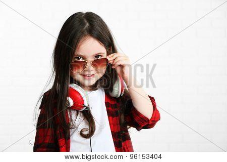 Beautiful little girl with headphones in room