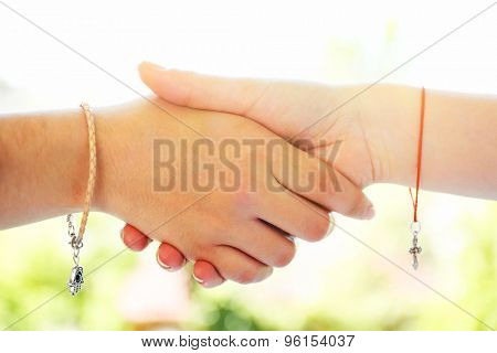 Two hands of friendship and religions symbols