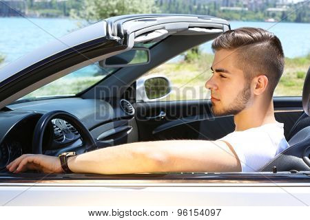 Young man in cabriolet, outdoors