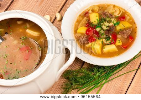 Hungarian hot soup on the wooden background.
