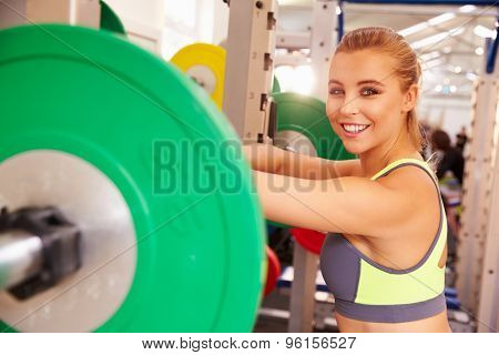 Woman leaning at a squat rack in a gym, smiling to camera