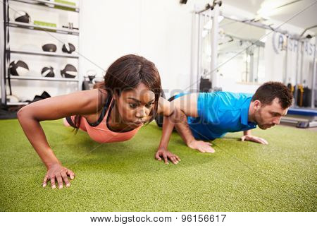 Man and a woman doing push ups at a gym