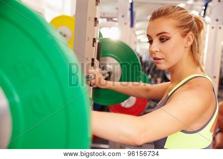 Woman preparing to lift barbells at a squat rack in a gym