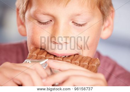 Close Up Of Boy Eating Bar Of Chocolate
