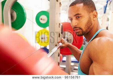 Man contemplating barbells on a rack at a gym