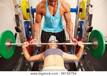 Woman bench pressing weights with assistance of trainer, front view