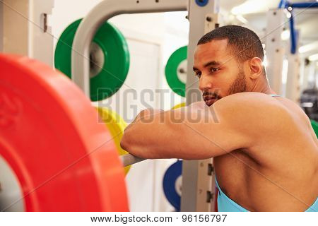 Man leaning on barbells in a rack after weightlifting at gym