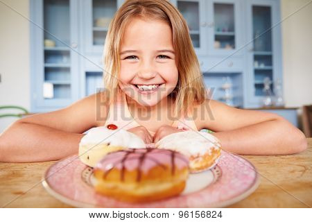 Young Girl Sitting At Table Looking At Plate Of Sugary Cakes