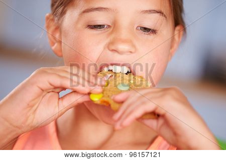 Close Up Of Young Girl Sitting At Table Eating Cookie