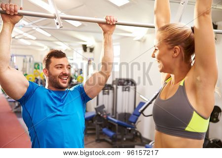 Man and woman reaching up to monkey bars at a gym