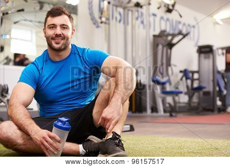 Young man drinking water in a gym