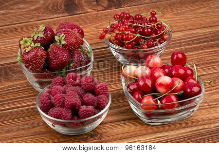 Strawberries, raspberries, currants and cherries in the cups on the wooden background.