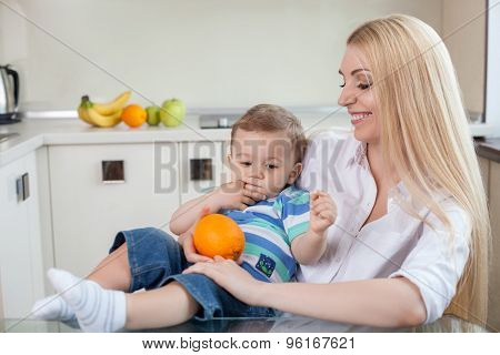 Beautiful young mother with her child in the kitchen