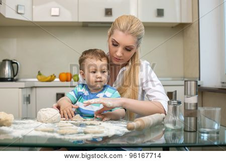 Young beautiful mother is teaching her child to cook