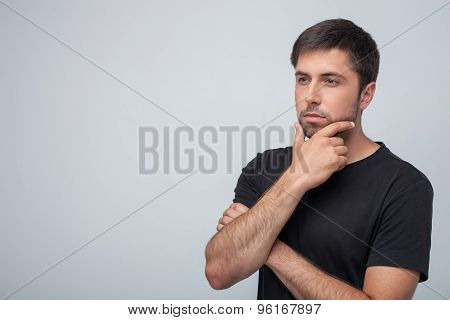 Cheerful young guy is thinking about his life