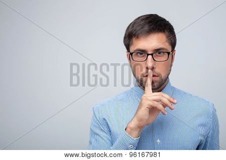 Cheerful young healthy guy is gesturing secretly