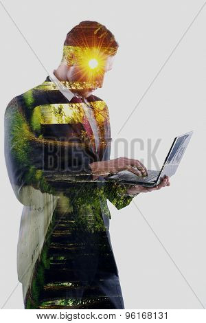 double exposure of business man who working on laptop computer  and alley with trees and sunrise