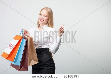 Cheerful young girl is doing shopping happily