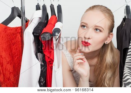 Beautiful young woman is choosing clothing in store