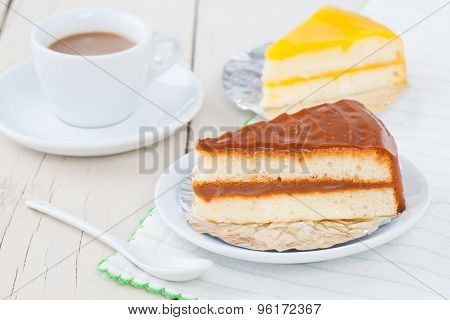 Coffee Cake On White Plate On Wooden Table With Coffee And Orange Cake