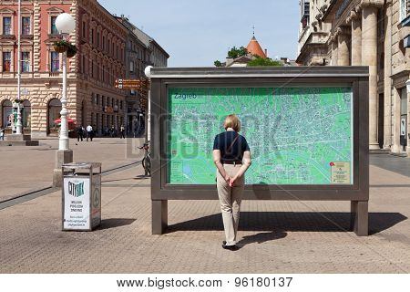ZAGREB, CROATIA - MAY 13, 2015: Woman standing in front of Zagreb city map at Ban Jelacic Square