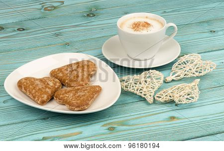 A cup of coffee with gingerbread on the wooden background.