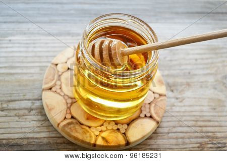 Golden honey with honeystick. cinnamon and anise stars on wooden table