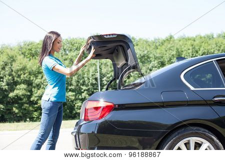 Beautiful young girl is opening a boot of the car