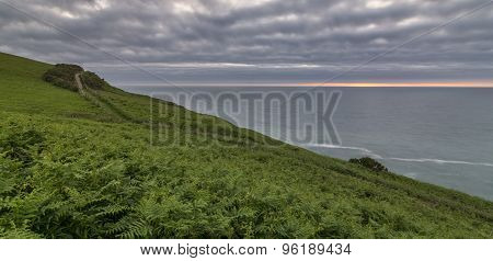 UK coastal path view, with a cloudy sky and a thin sunset