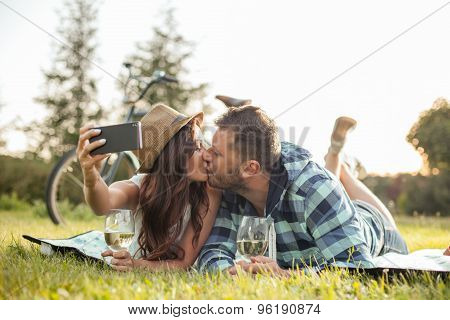 Cute young loving couple are photographing themselves in the nature