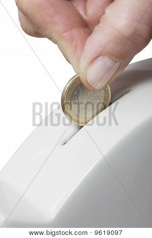 hand putting one coin in a piggy bank