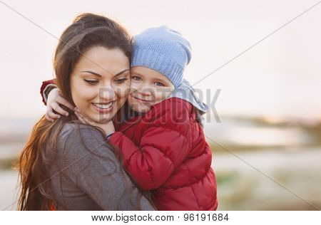Happy Mum And Baby Girl Walking At Beach In Autumn