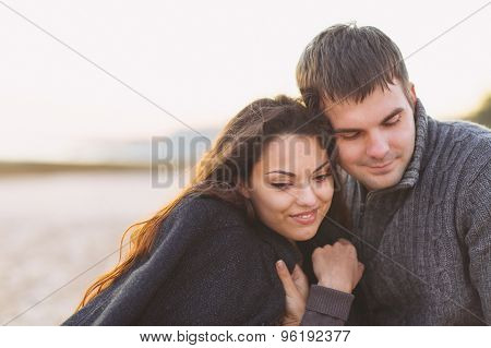 Portrait Of Young Happy Couple Laughing In A Cold Day By The Autumn Sea