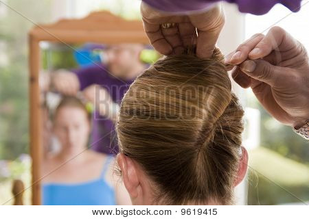 Hairdresser preparing bride for wedding