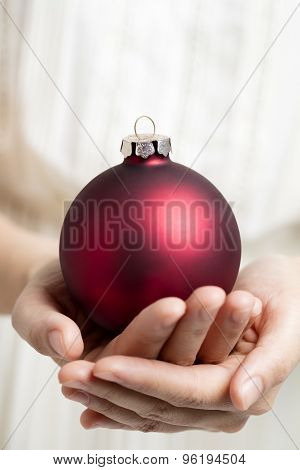Christmas ball holding by hands
