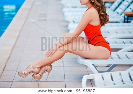 Perfect, sexy legs and ass of young woman wearing seductive red swimsuit