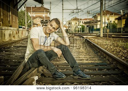 Attractive young man sitting on railroad smiling